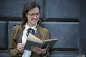 happy-adult-woman-reading-book-with-interest-on-street-3772711